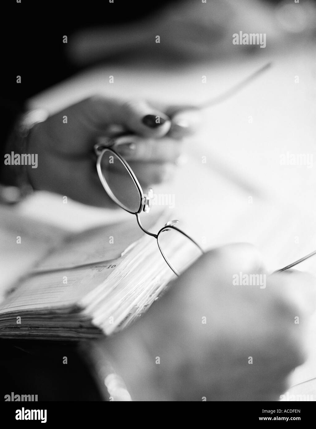 Female hands holding a pair of glasses close-up BW. - Stock Image