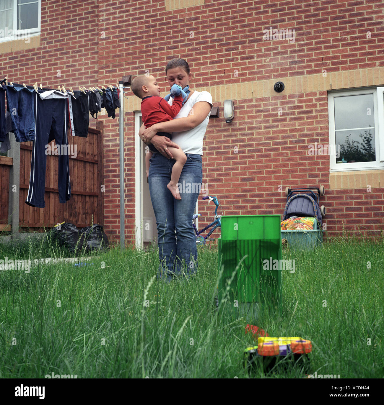 A single mother with her son in the garden of her new home, Bristol, UK. - Stock Image