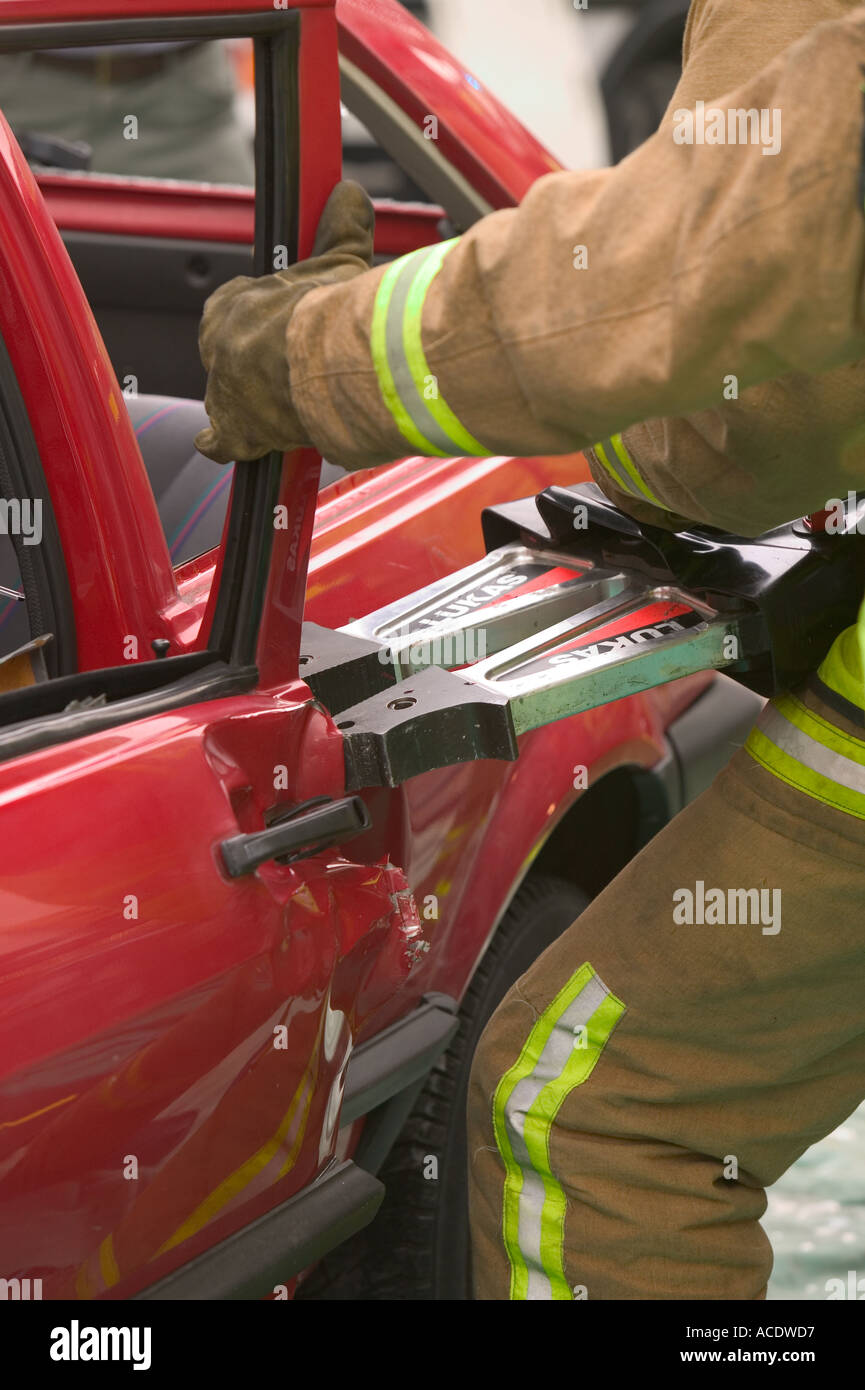 Fireman using the Jaws of Life to gain access to a car crash victim - Stock Image