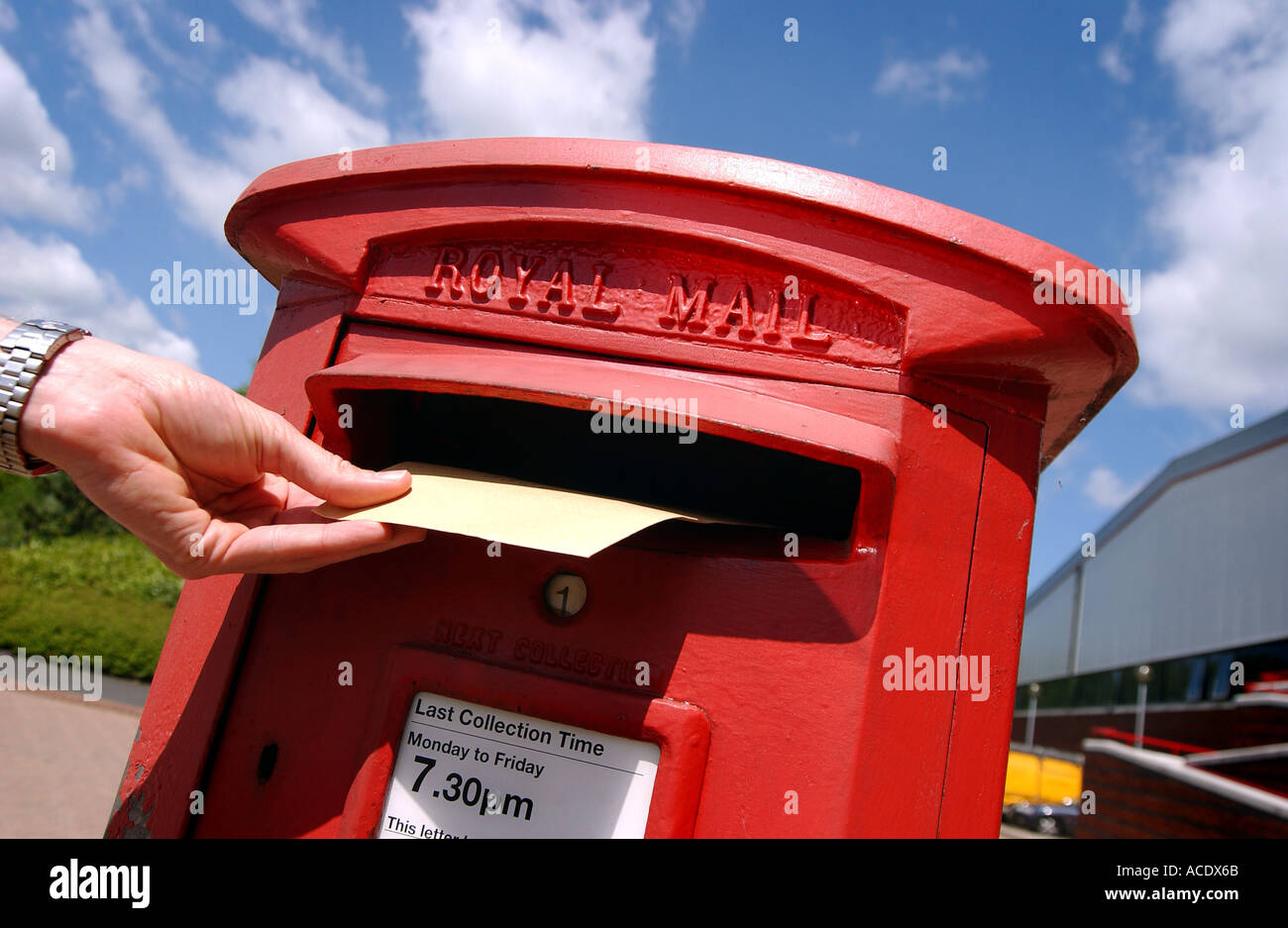 A hand posting a letter into a royal mail postbox on a sunny day - Stock Image