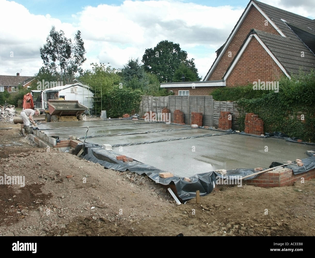 Labourer working on wet recently delivered ready mixed concrete floor slab pour into plastic sheeting damp proof membrane awaits edge trimming UK - Stock Image