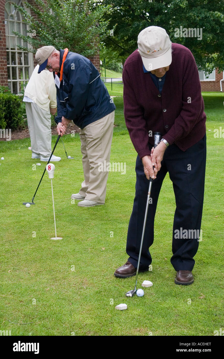 Several retired elderly men in their 80s bending over to putt golf balls into the holes on a putting green - Stock Image