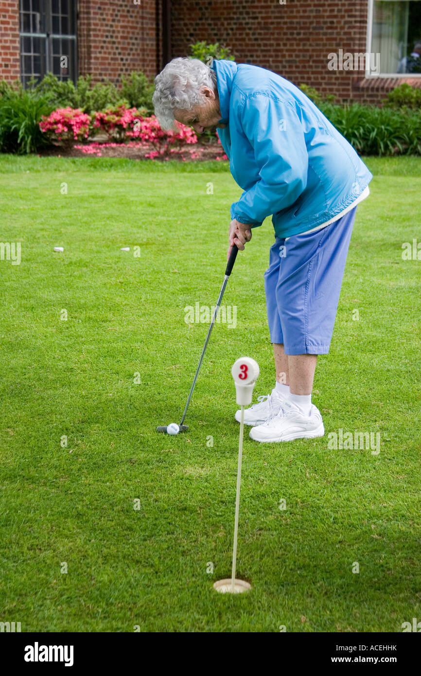 Elderly retired woman in her 80s bending over to putt a golf ball into the hole - Stock Image