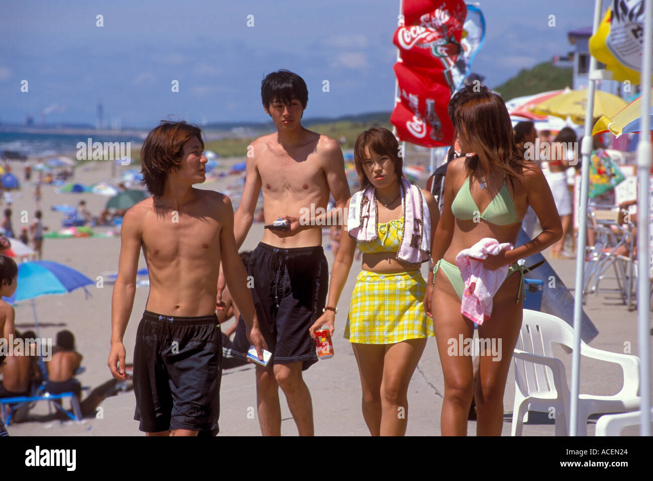 Two couples wearing swimsuits walk along the beach at the Sea of Japan Stock Photo
