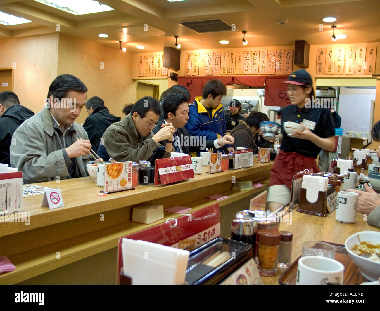 Inside a small local eatery for people on the go sitting at a counter - Stock Image