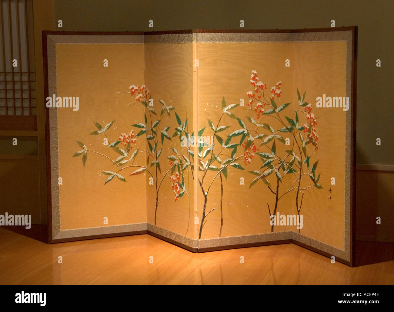 Antique folding screen with winter flower scene against gold background Stock Photo