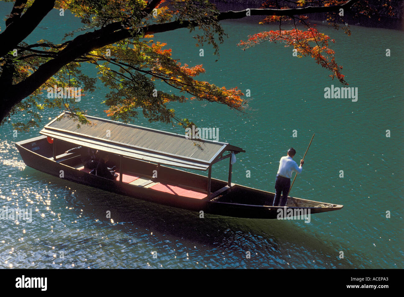 Boatman steering human powered boat up the Hozu River in Kyoto - Stock Image