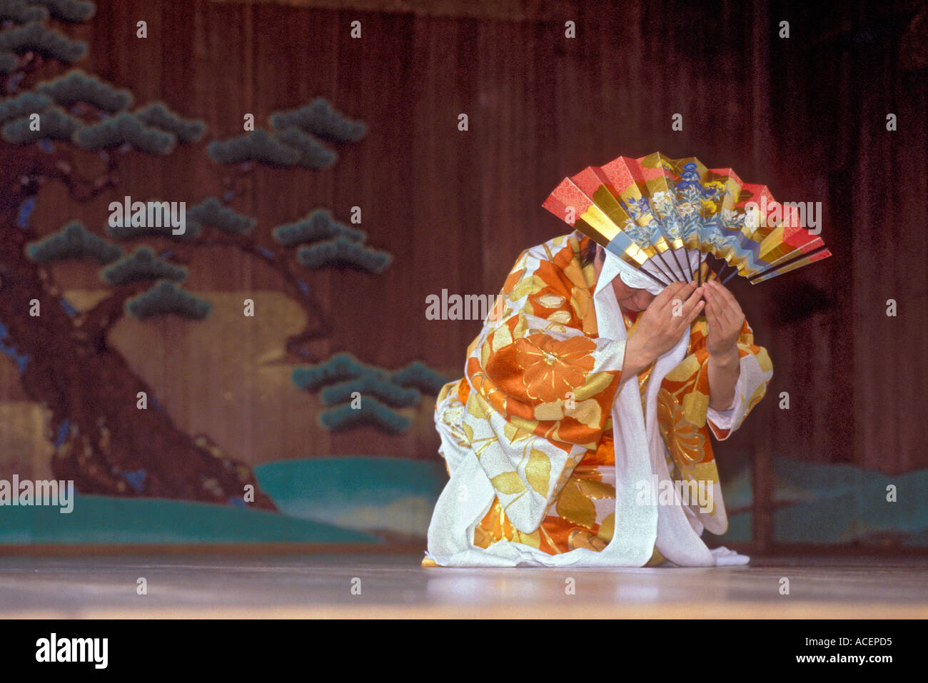 Performer In Traditional Noh Costume Holding Fan Executes A Move During A Kyogen Play Stock