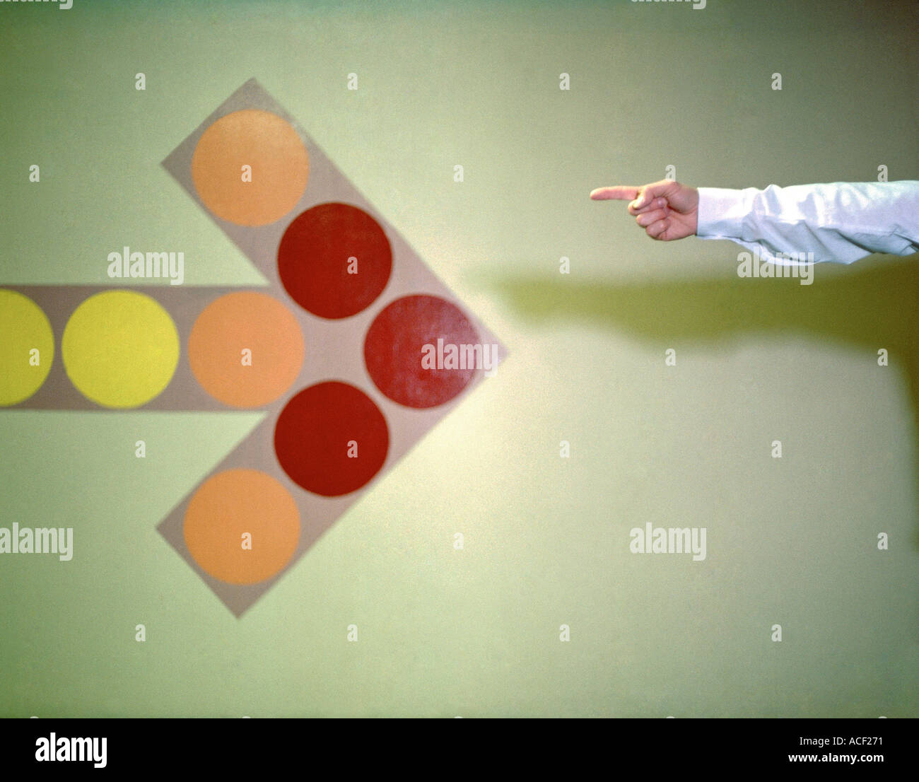 Arm of businessman pointing at arrow on wall Model Released - Stock Image