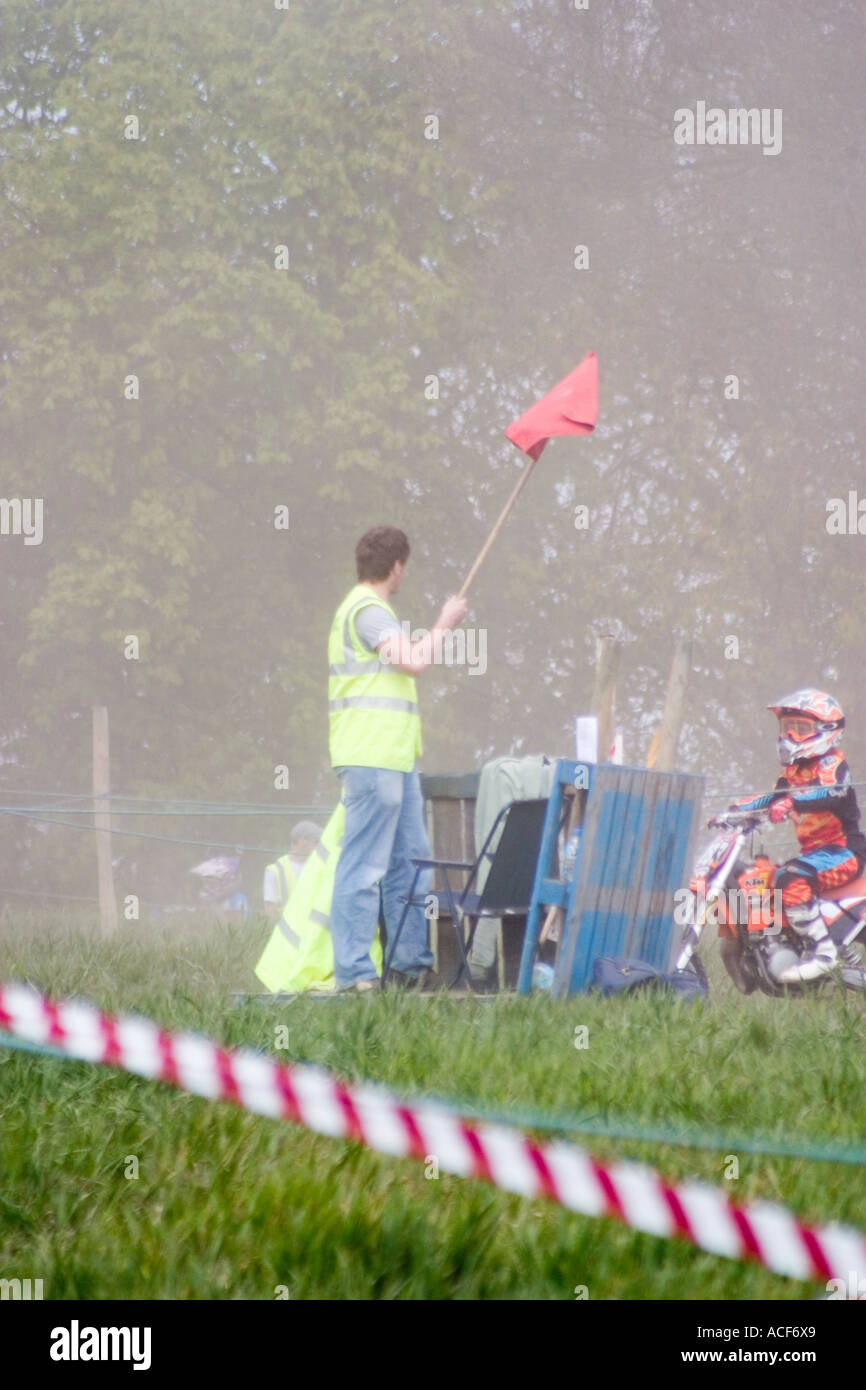 Marshall at Motocross race waving red flag to stop race - Stock Image