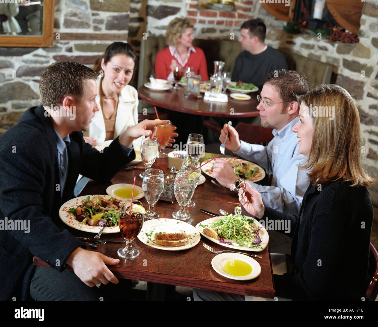 Two couples having a conversation while dining together at a restaurant Another couple sits in a corner booth behind them - Stock Image