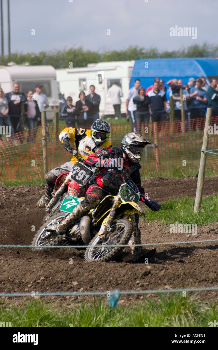 Group of Motocross riders cornering during race - Stock Image