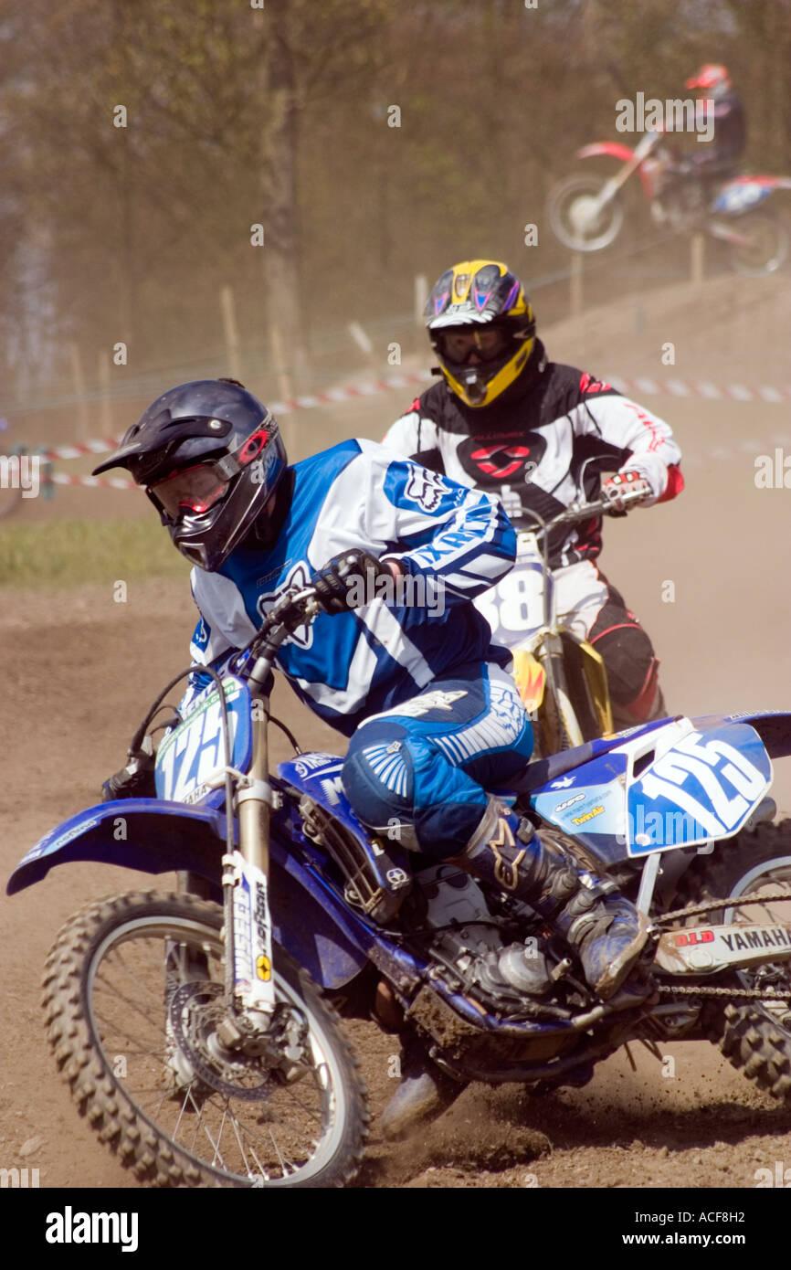 Motocross rider cornering during race - Stock Image