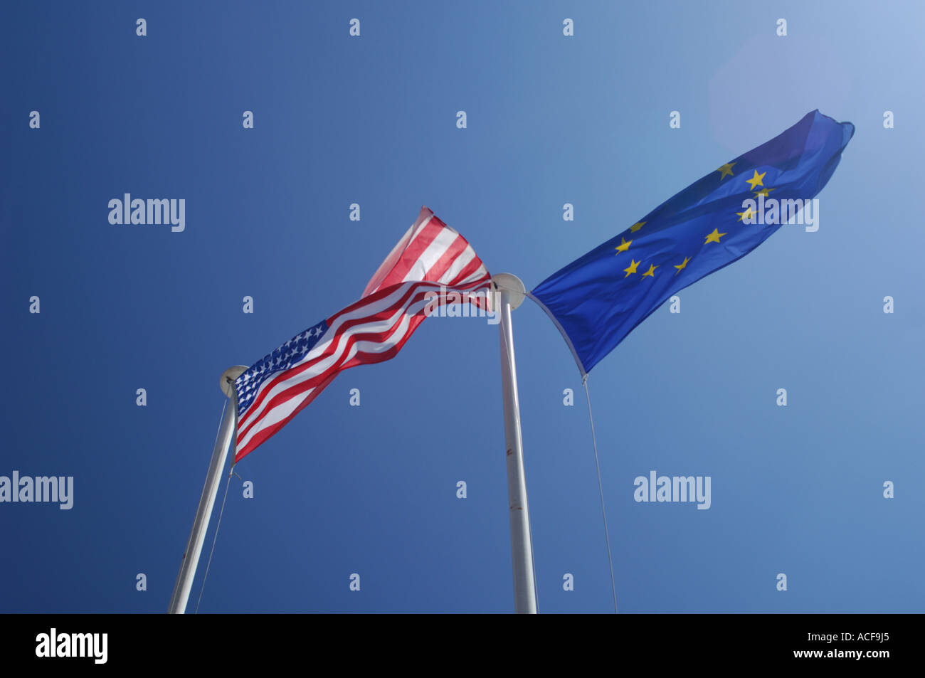 United States and European Union flags flying side by side in a blue sky - Stock Image