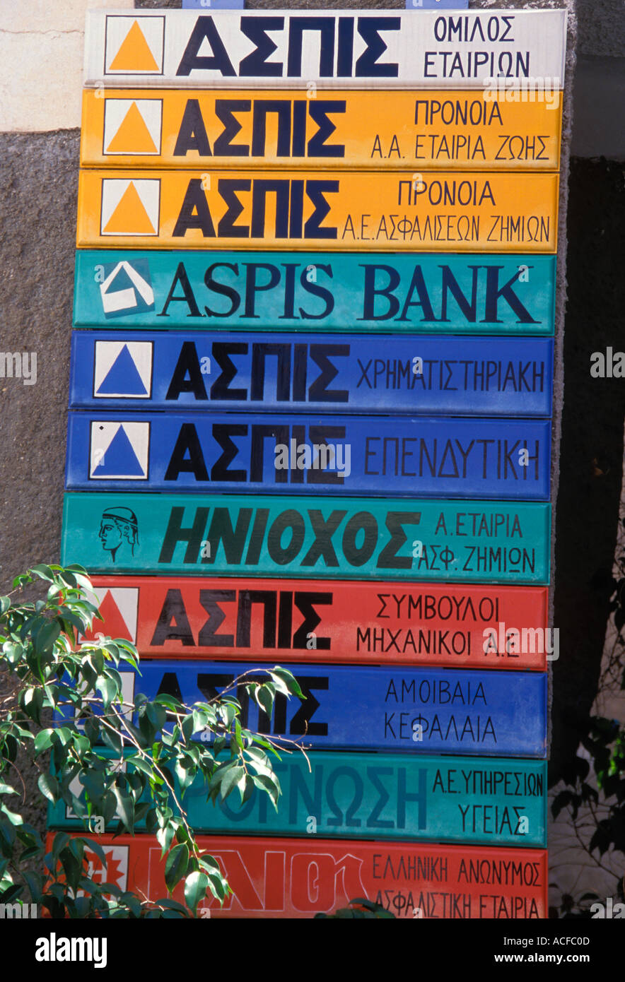 Greek language signs of various businesses in yellow blue red turquoise on isle of Poros on the Peloponnesus of  Greece Europe - Stock Image