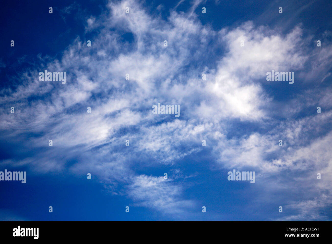 White Cirrus clouds in a bright blue polarised sky Stock Photo