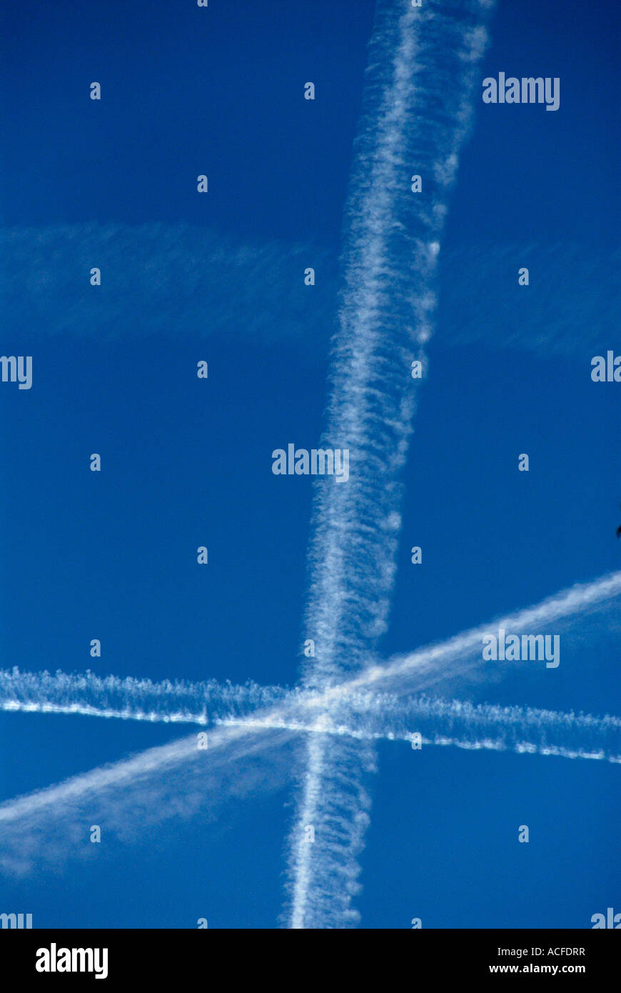 Contrails of some airplanes in blue sky - Stock Image