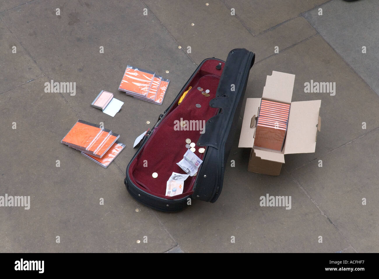 Violin case openon the ground with money earned from busking and boxes of cd s for sale beside it - Stock Image