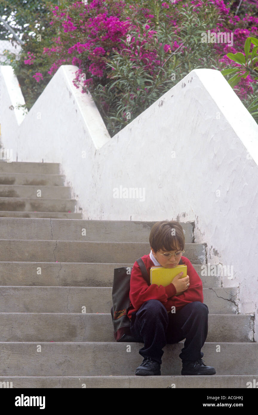 SCHOOL SAD STEPS BOY UNIFORM BULLIED EXAMS Pensive junior schoolboy with study folder sits alone in thought on steps - Stock Image