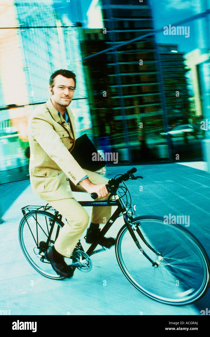 Man on a bike with attachà case building in the background - Stock Image
