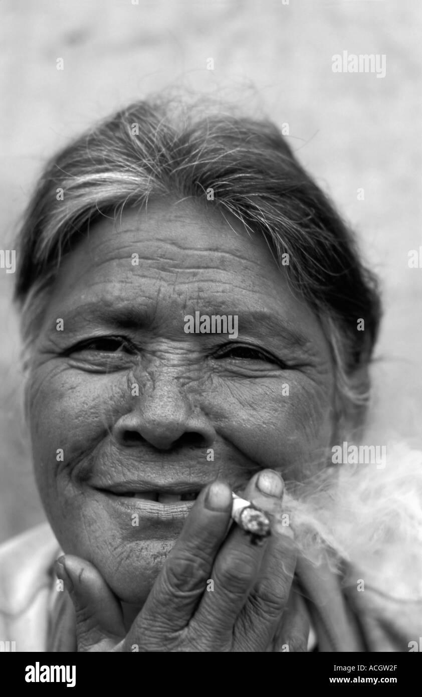Friendly elderly vendor smoking a cheroot Market Pyin U Lwin Maymyo Central Burma Monochrome photograph - Stock Image