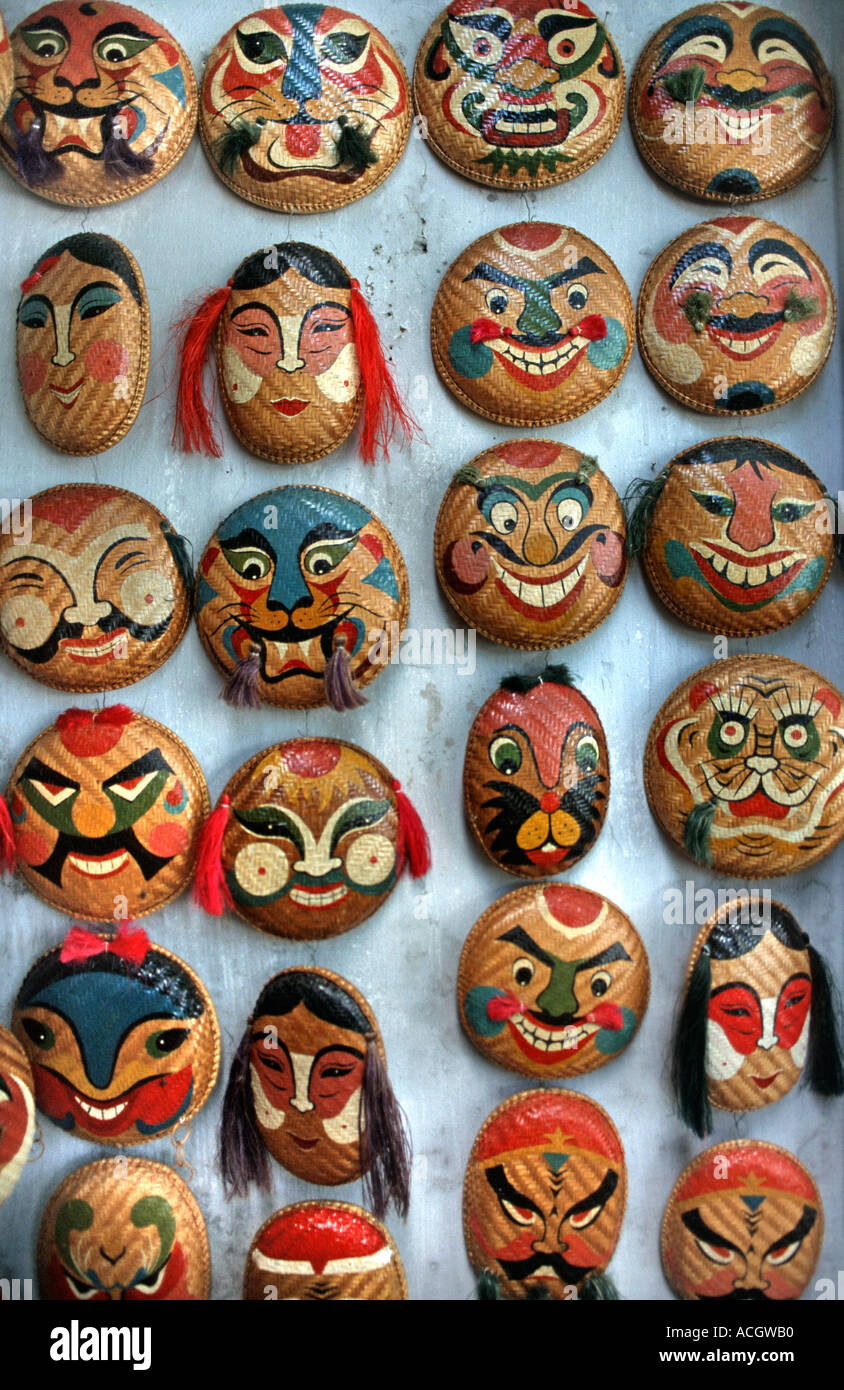 Selection of colourful hand painted Vietnamese masks for sale on a market stall in Hanoi Vietnam - Stock Image