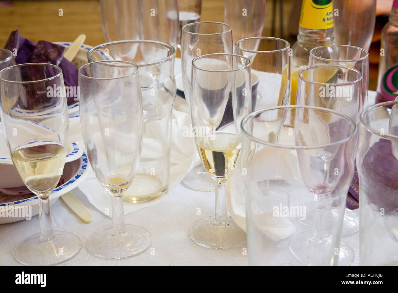 Dirty glasses and used paper plates on a bar top waiting to be washed after a party UK & Dirty glasses and used paper plates on a bar top waiting to be ...