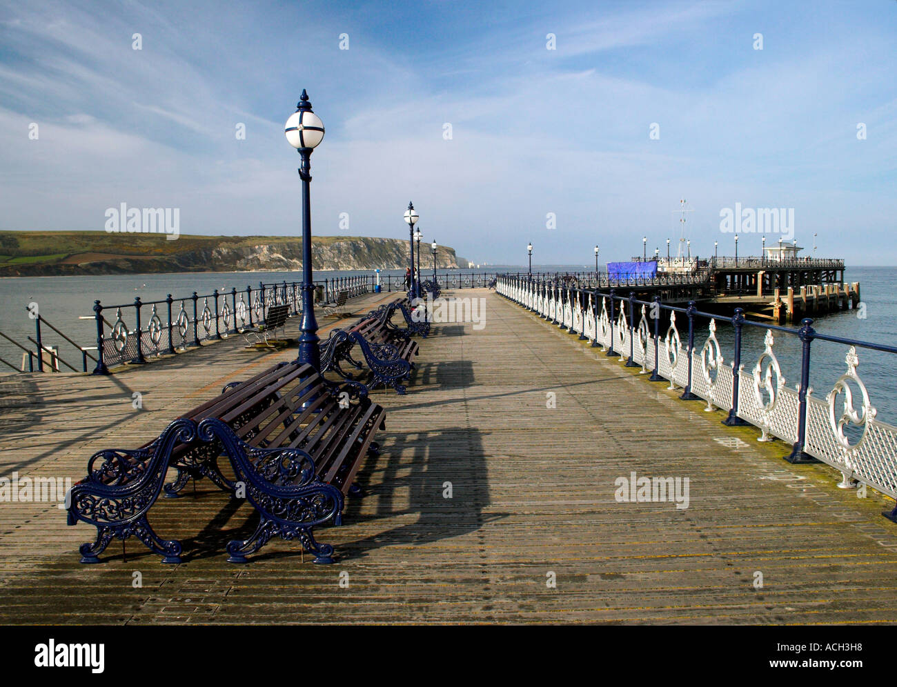 Swanage Pier Dorset on summer's day looking out to sea with blue ray clouded sky - Stock Image