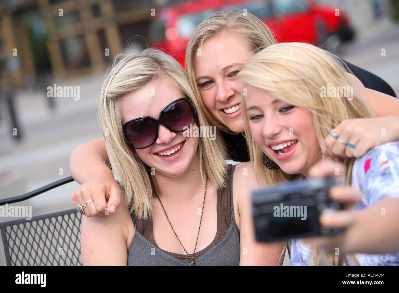 Three girls talking a picture together - Stock Image