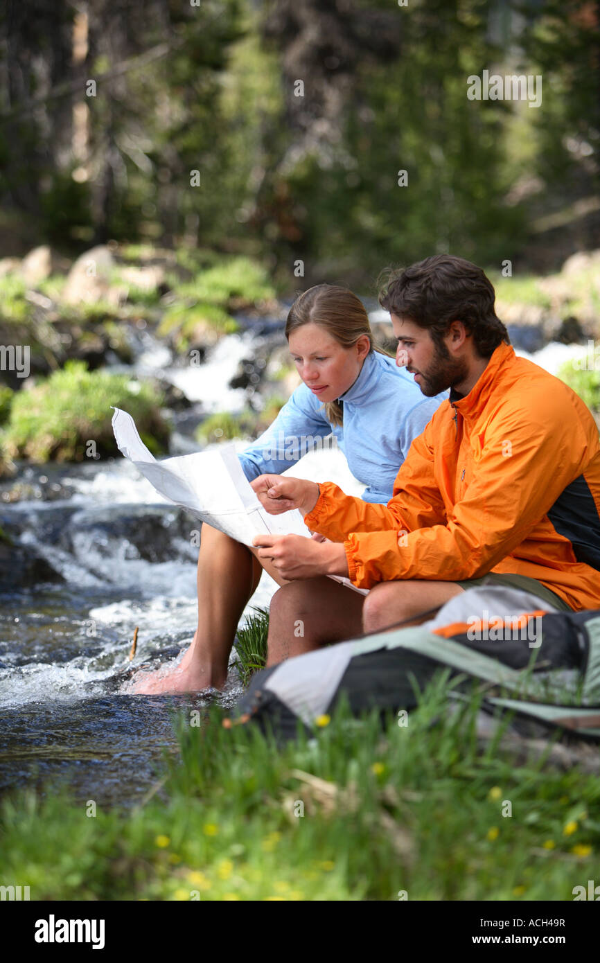 Backpacking couple sit down by a stream to look at map - Stock Image