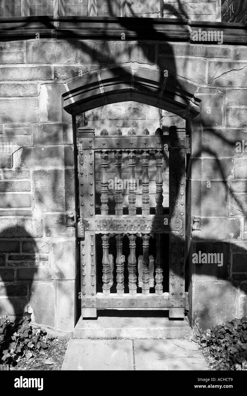 A solid wood and iron door with brick building. Locked and secure. shadow and light, black  and white photography. - Stock Image