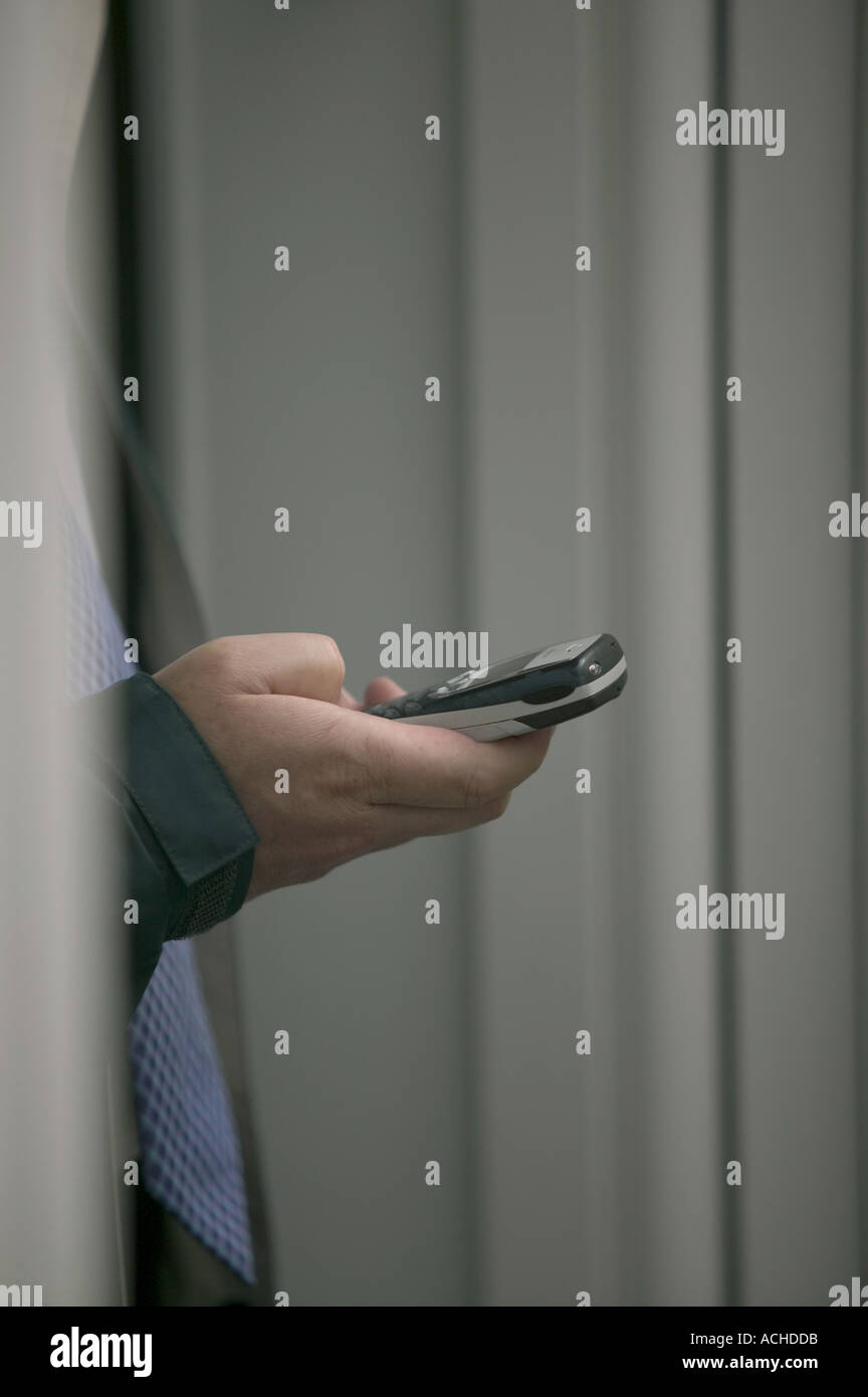 Man holding mobile phone in doorway - Stock Image