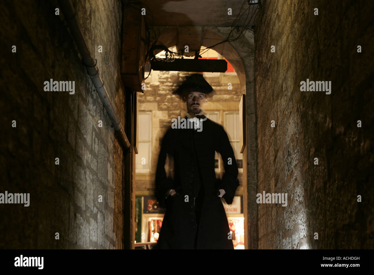 The shadowy figure of a man standing in a passageway. - Stock Image