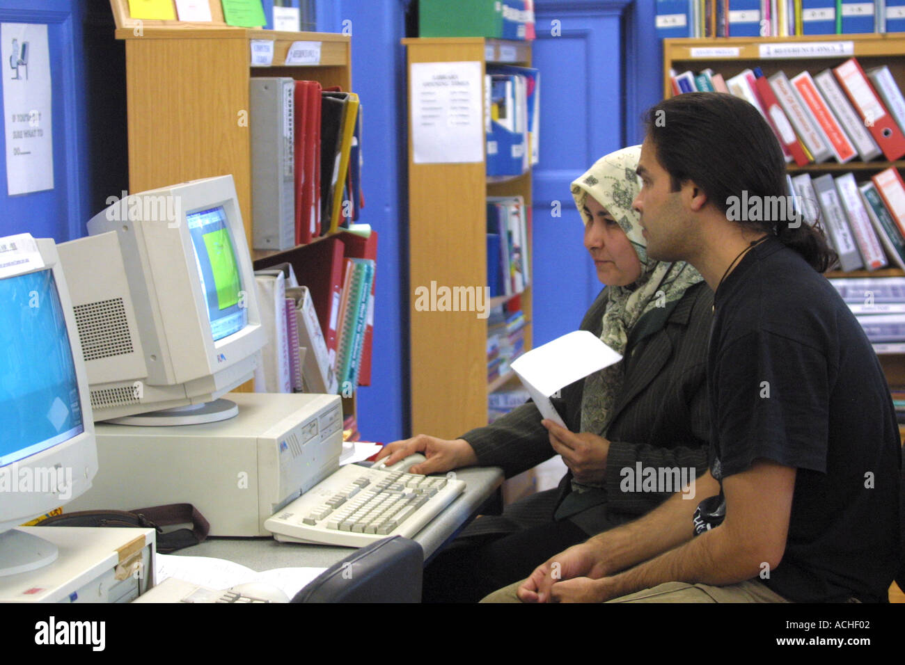 Mature female student wearing head scarf with instructor and computer  at  FE London college - Stock Image