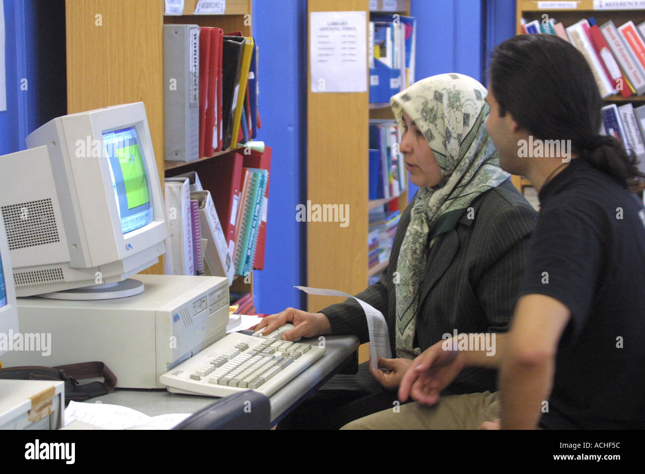 Mature female student wearing head scarf with instructor and computer  at  London college - Stock Image