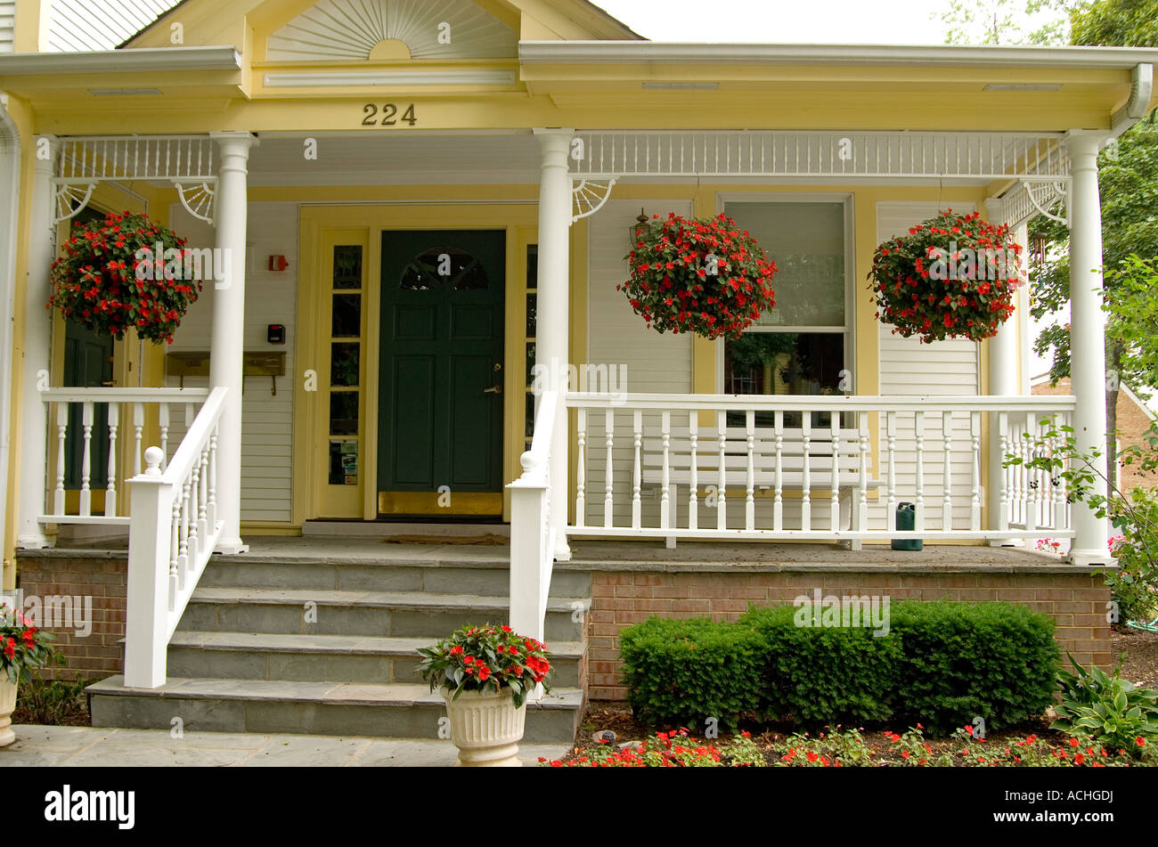 Victorian front porch with potted hanging plants
