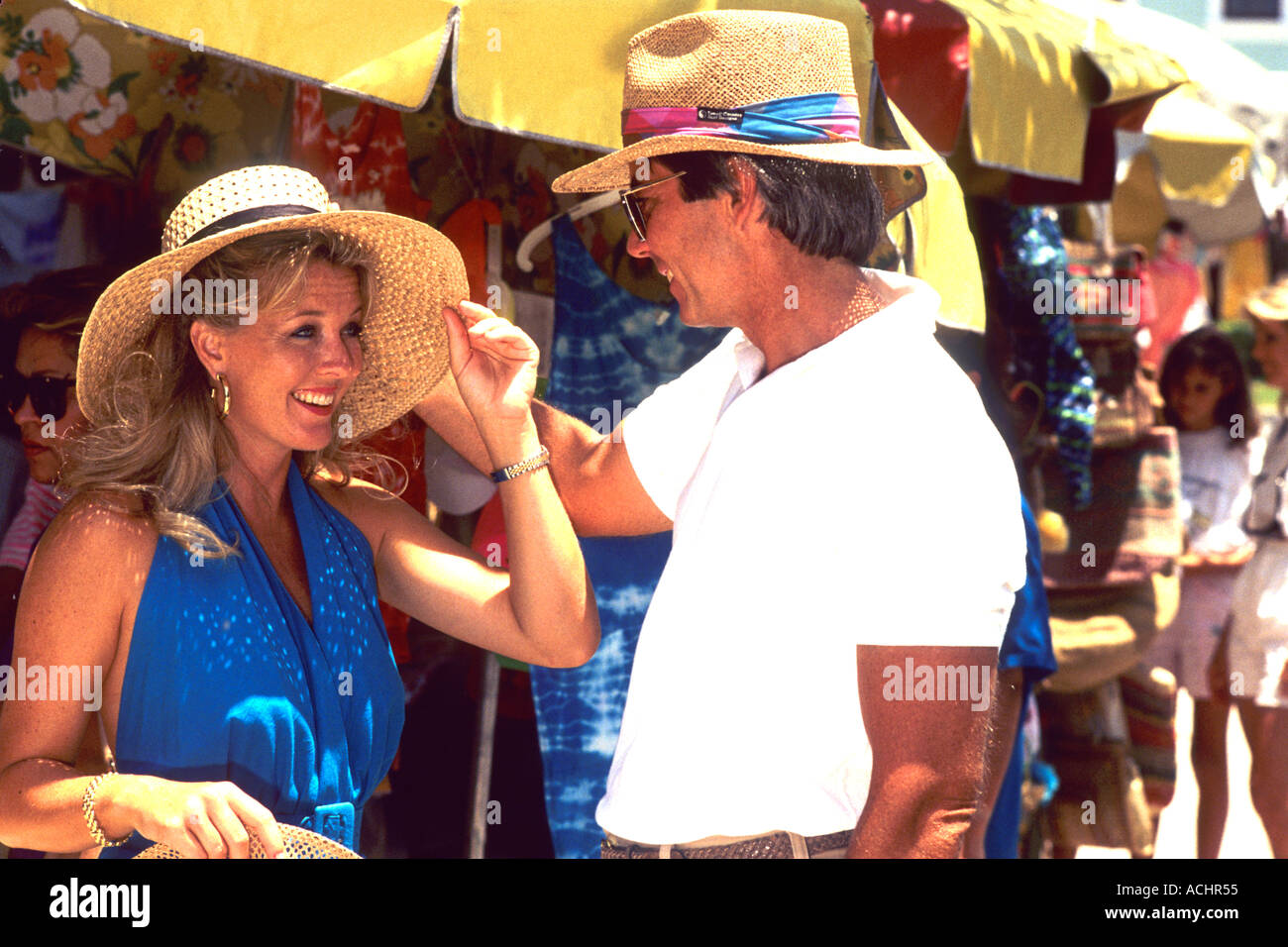 fb3dfd71b89 Colorful tourist couple shopping at island straw market Stock Photo ...