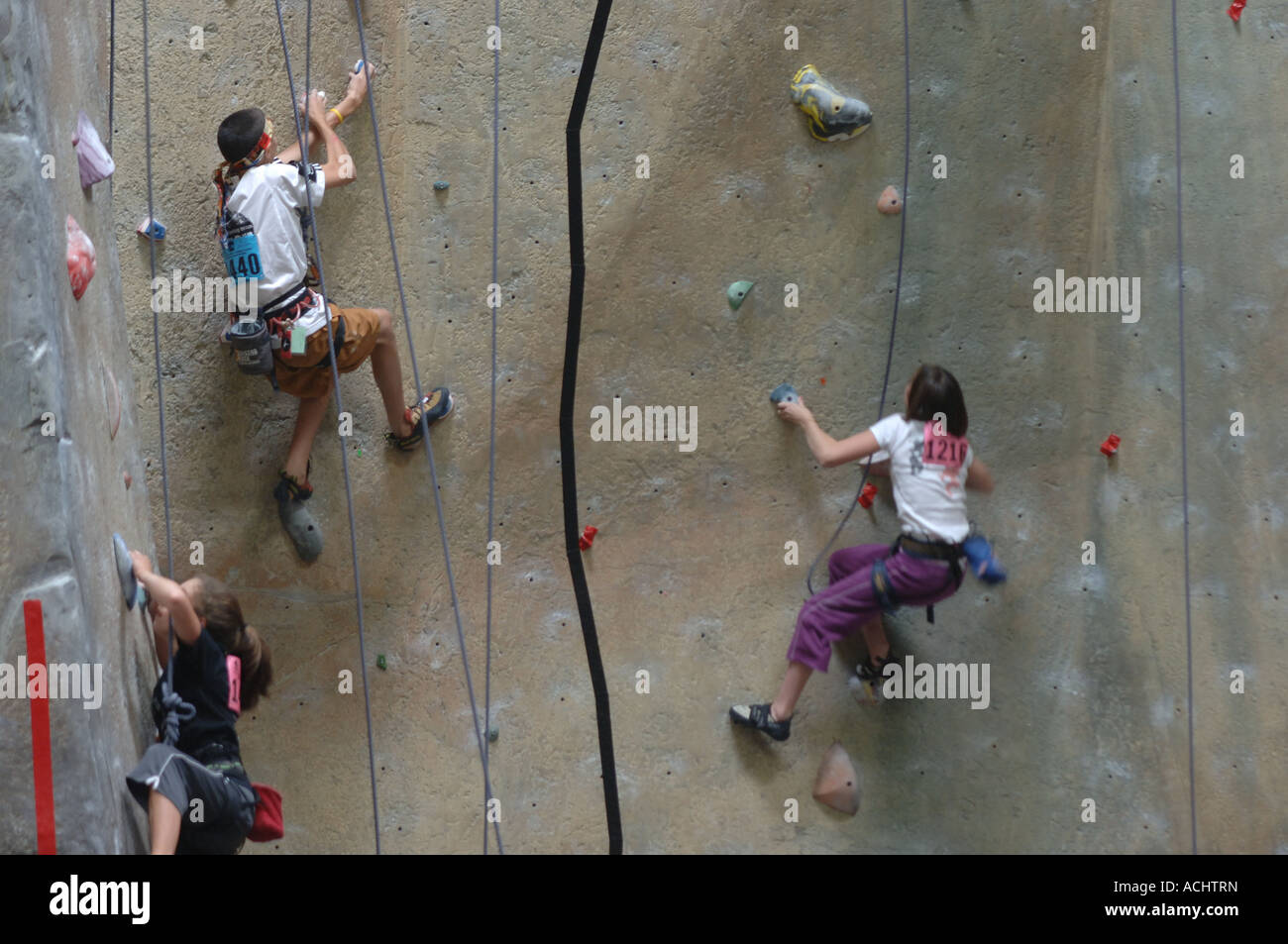 Young men and women climbing a wall at indoor climbing facility at a climbing competition - Stock Image