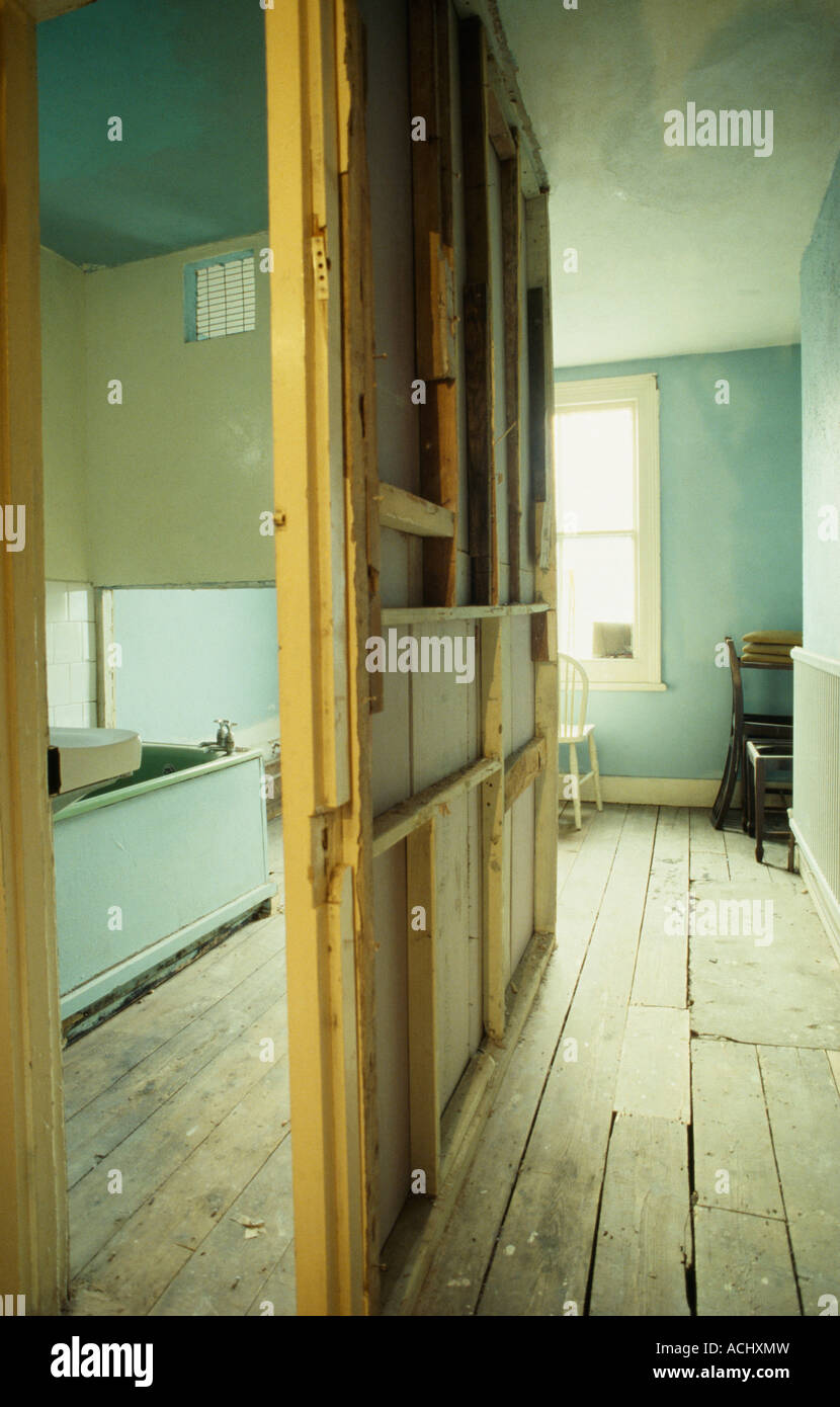 Dividing wall between two rooms with bare floorboards Stock Photo