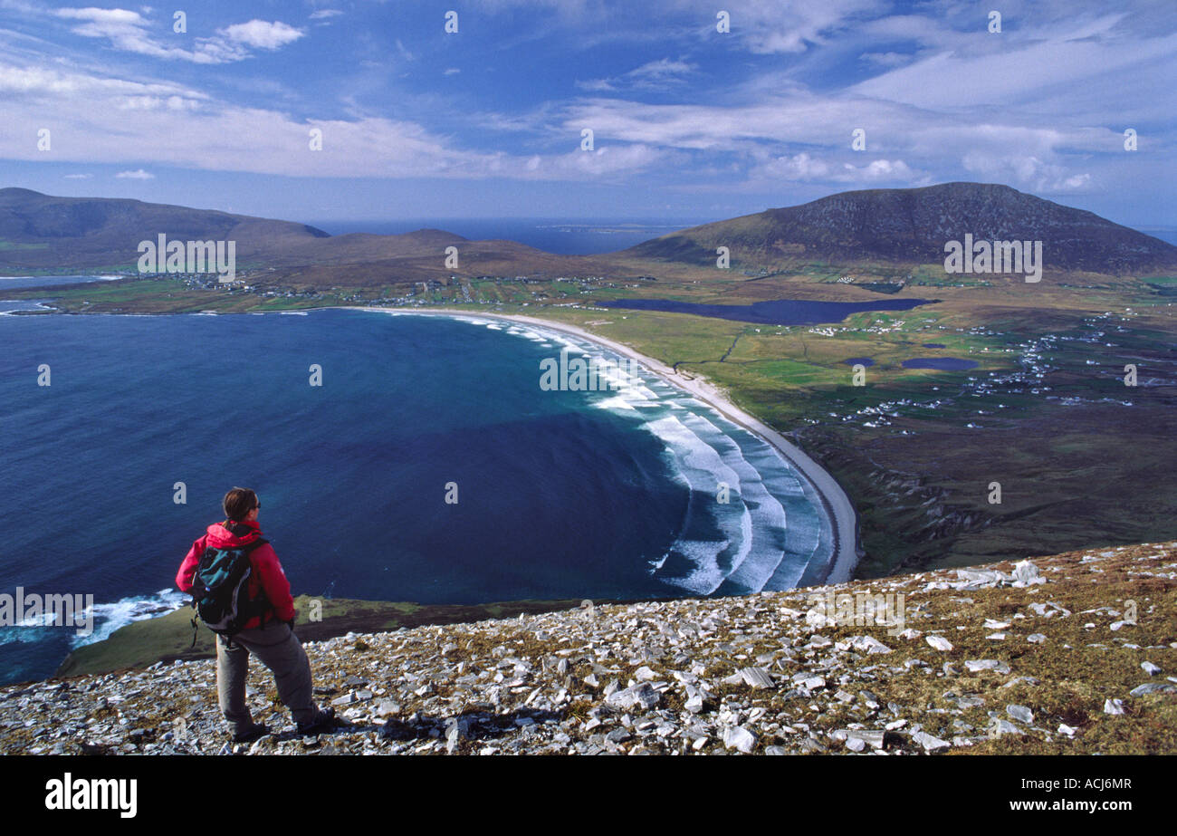 Walker looking over Keel Bay from the Menawn Cliffs. Achill Island, County Mayo, Ireland. - Stock Image