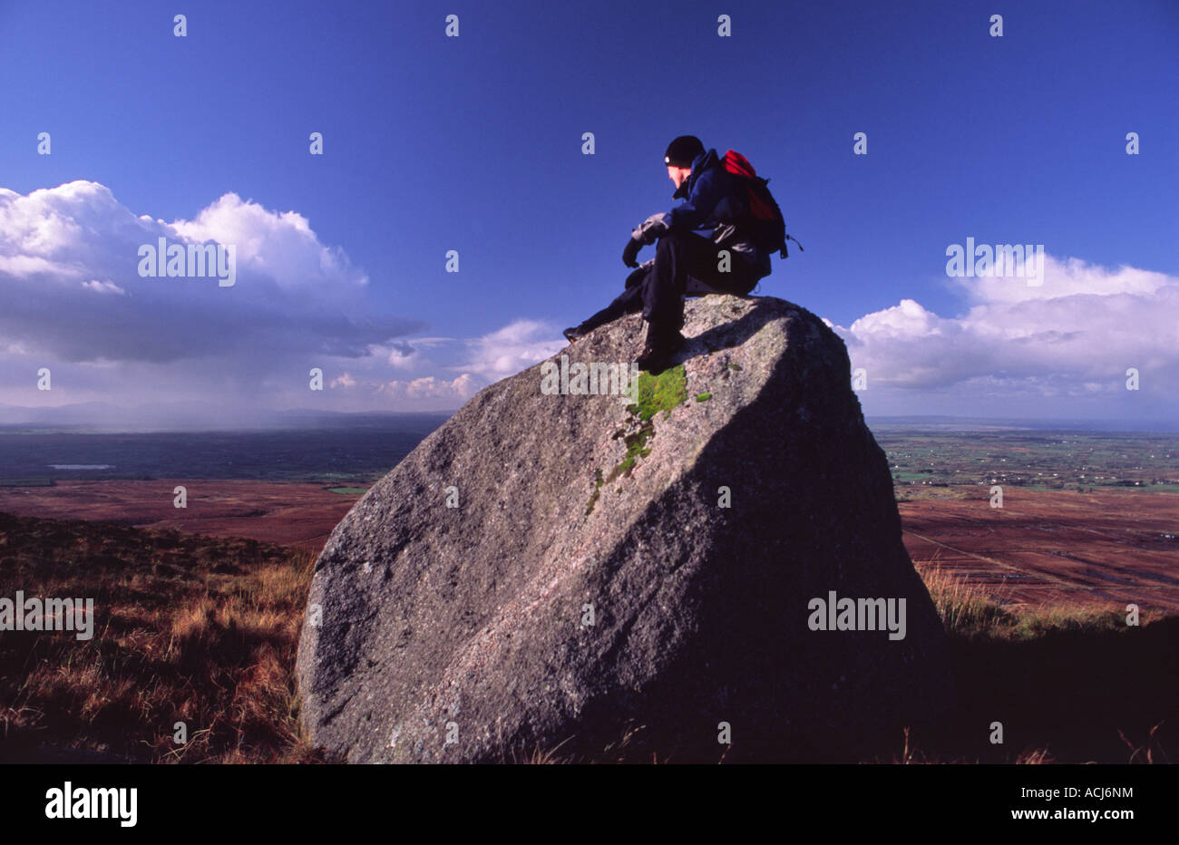 Walker on a glacial erratic boulder looking over Donegal Bay. Ox Mountains, County Sligo, Ireland. - Stock Image