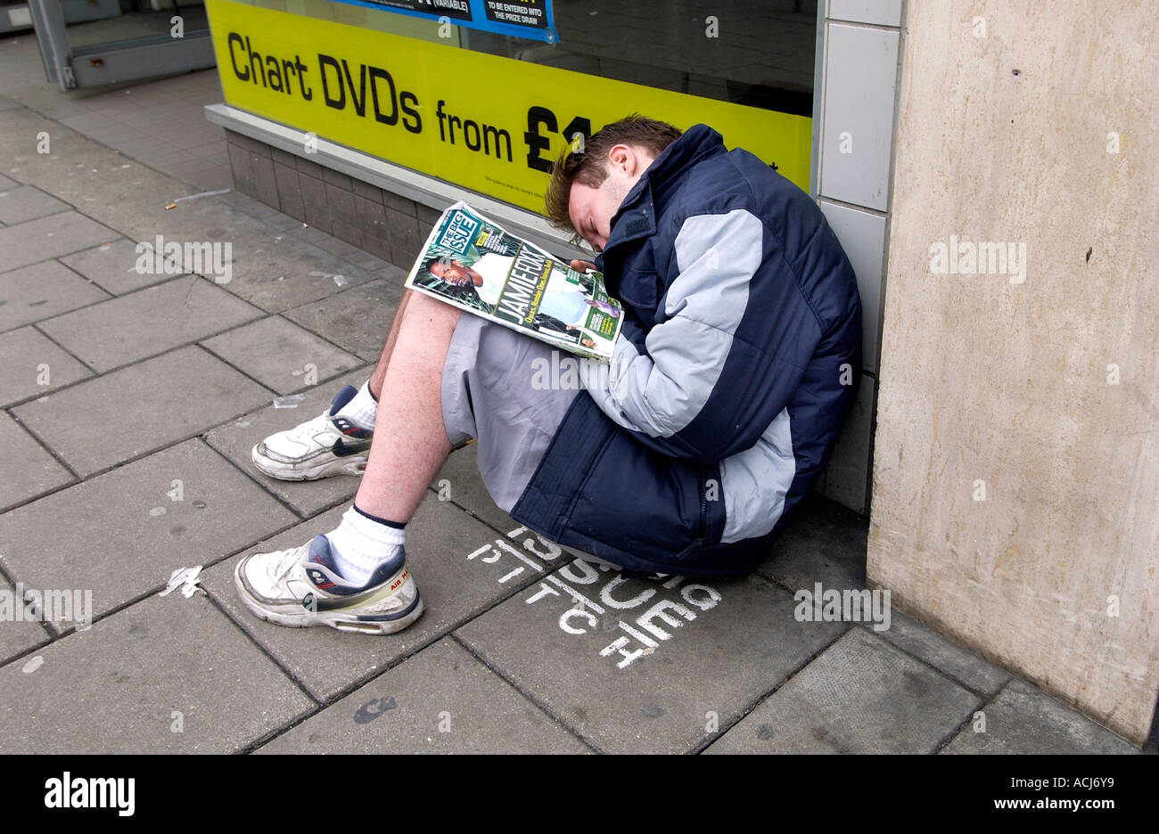 A Big Issue seller asleep on his pitch outside a HMV record shop in Western Road Brighton - Stock Image