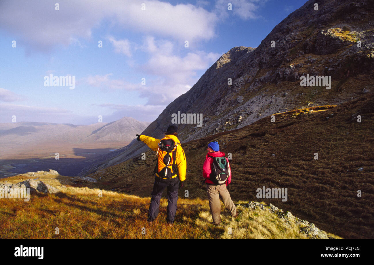 Walkers on the slopes of Bencollaghduf, Twelve Bens Mountains, Connemara, County Galway, Ireland. - Stock Image