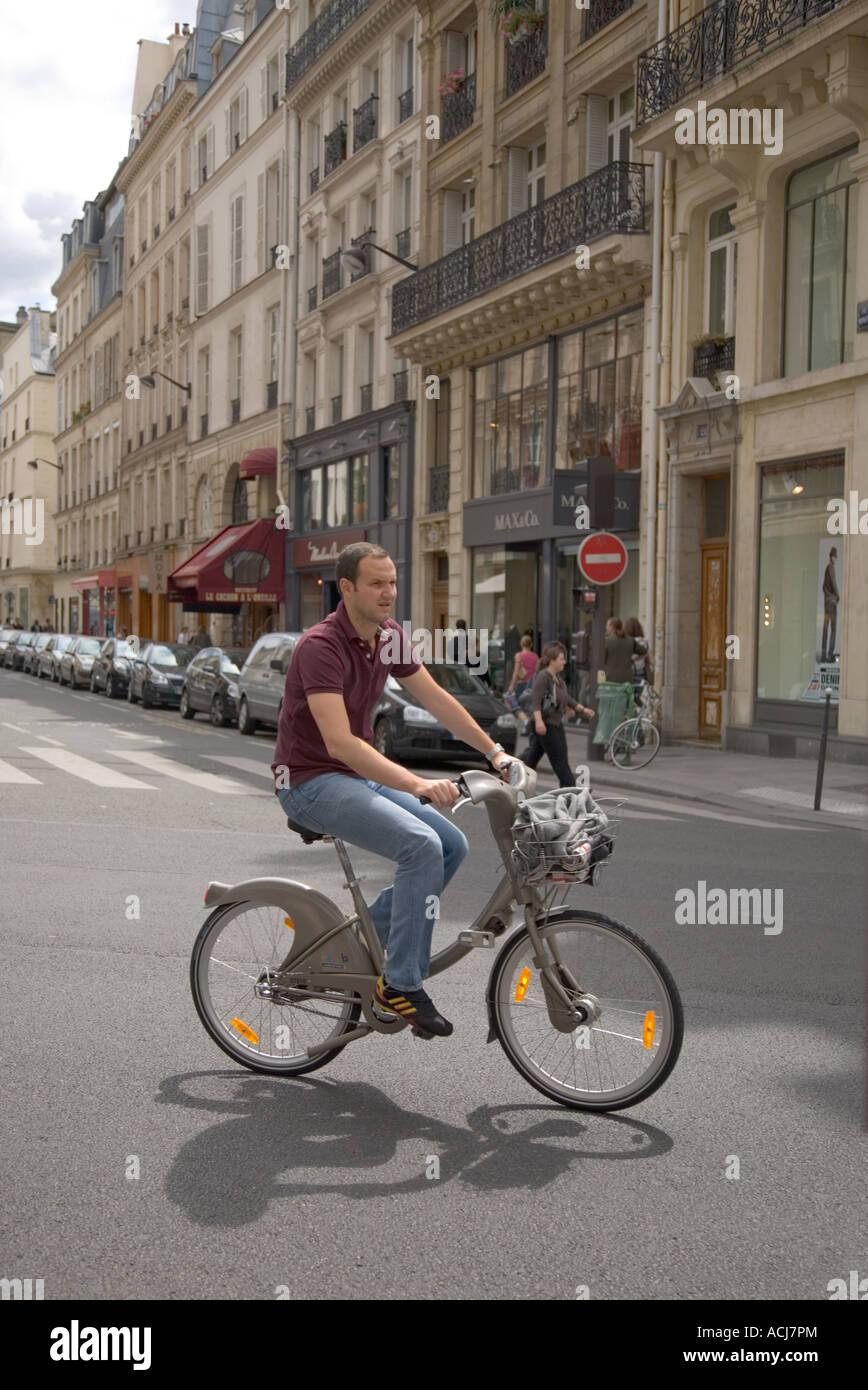 Velib public rental bike being ridden in Paris - Stock Image