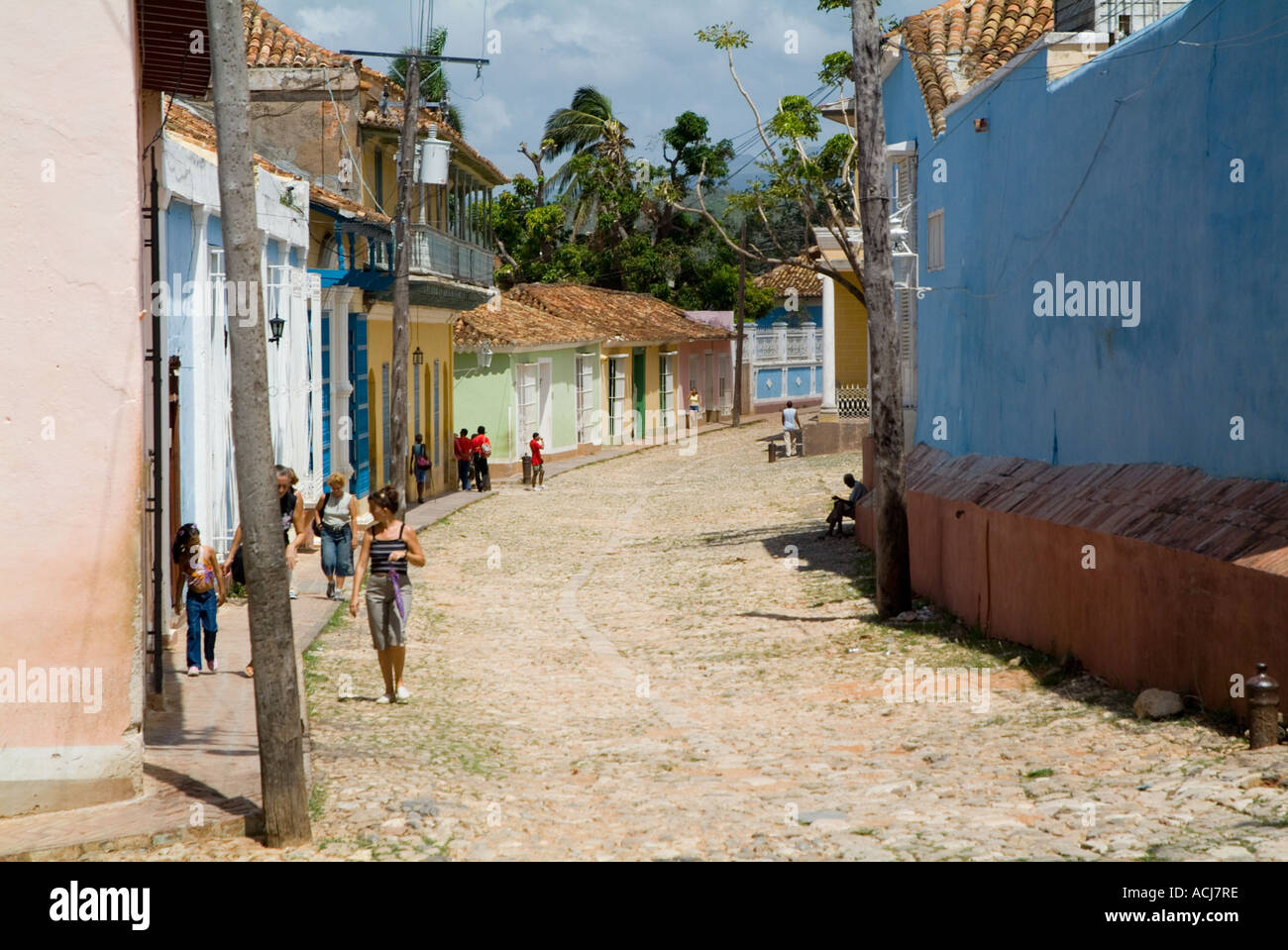 Couple walking past windows with metal grills on a cobbled street, Trinidad, Cuba. - Stock Image