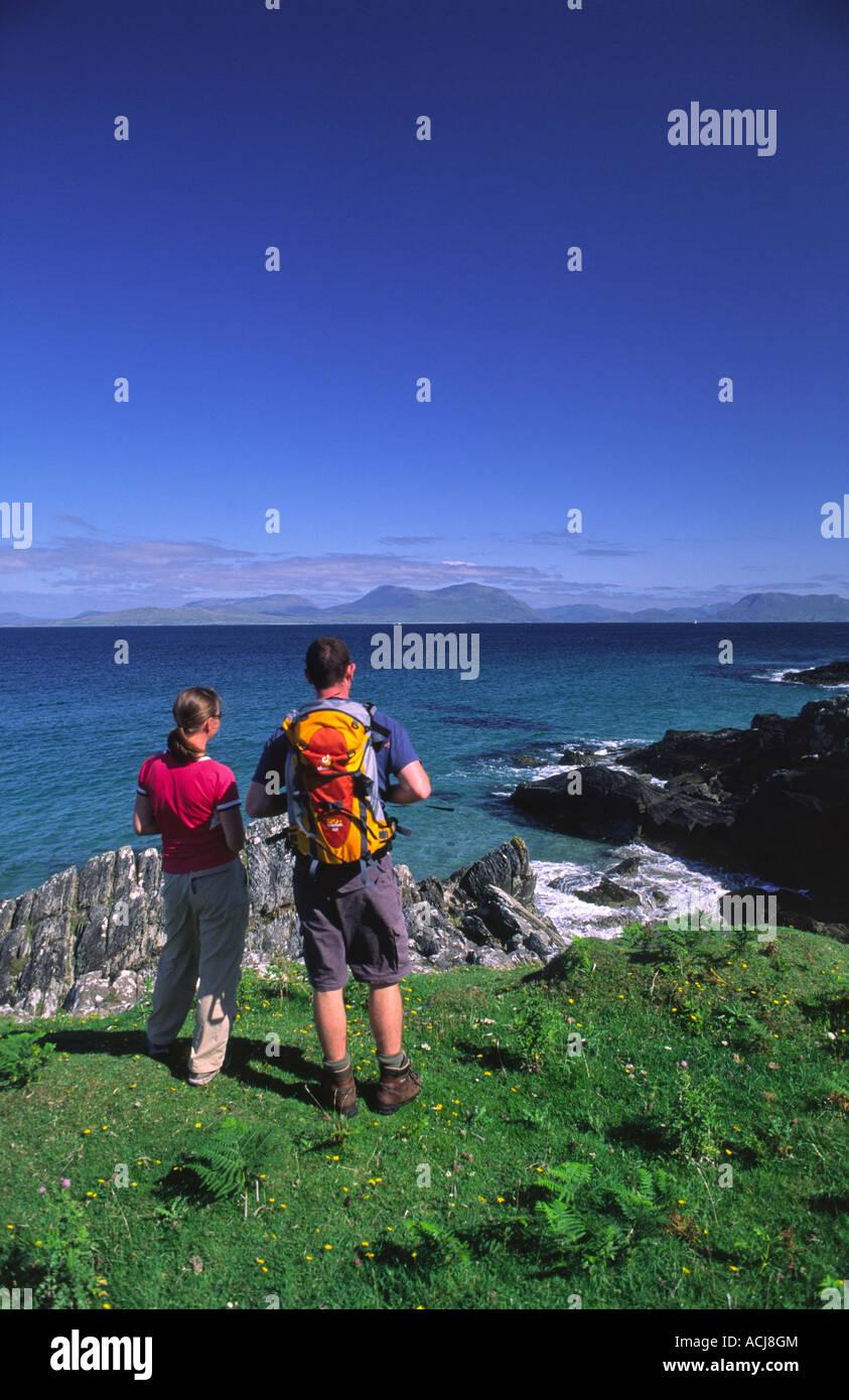 Summer coastal walkers looking towards the mainland from Inishturk Island, County Mayo, Ireland. - Stock Image