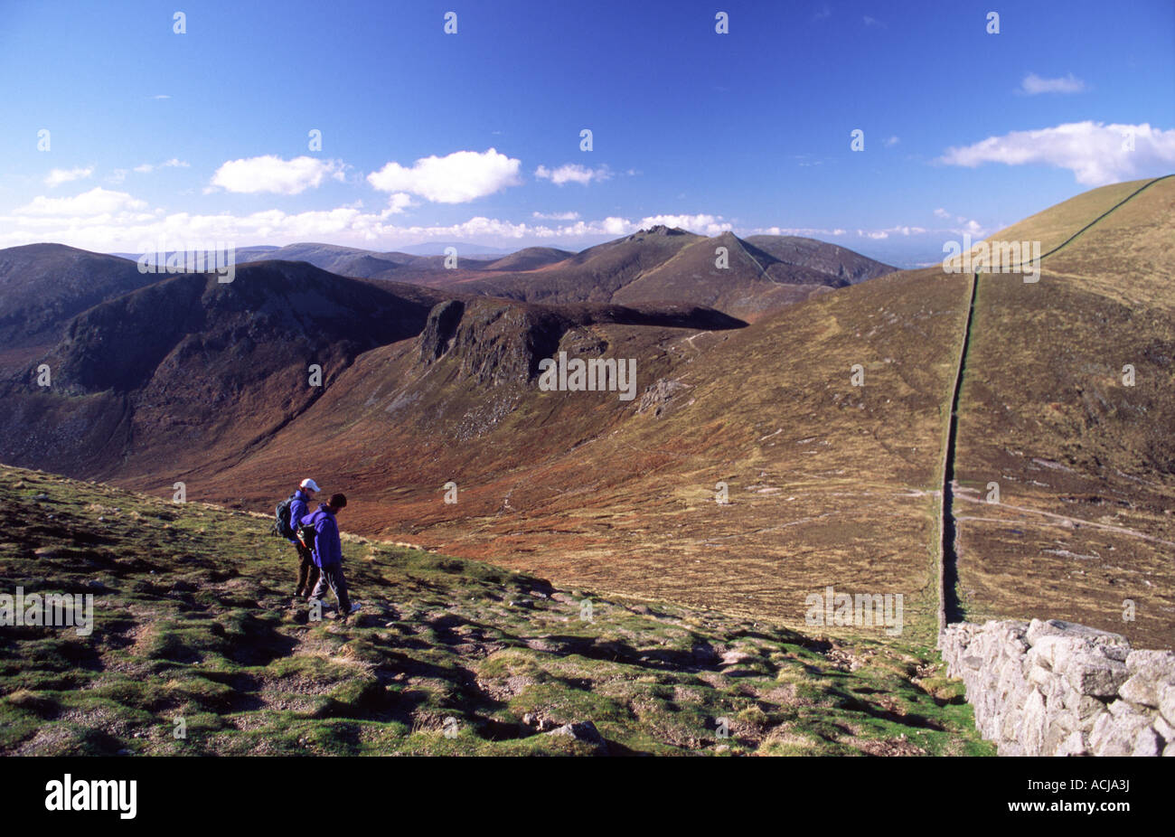 Walkers on the slopes of Slieve Donard, beside the Mourne Wall, County Down, Northern Ireland. - Stock Image