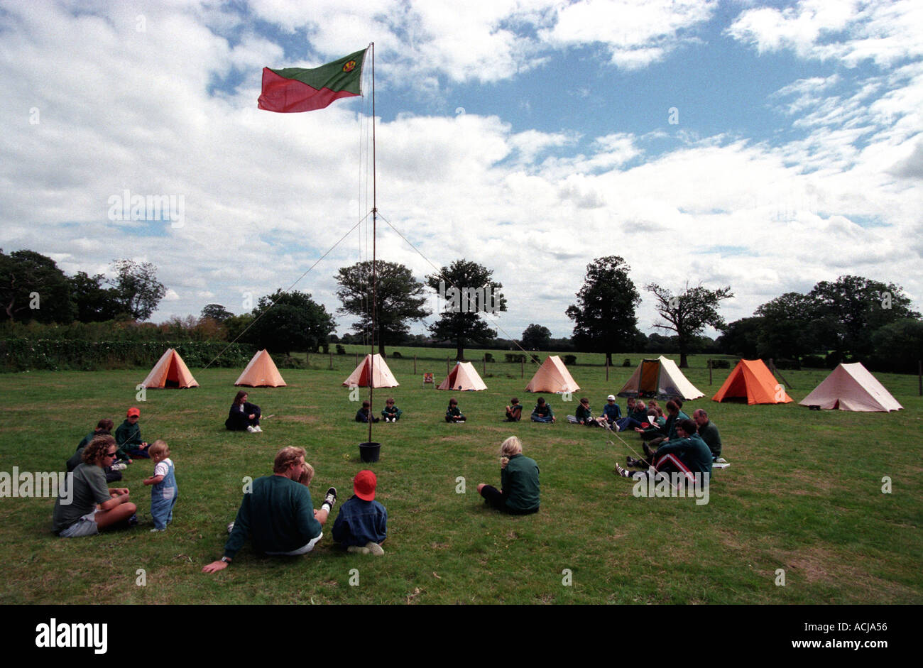 Woodcraft folk sitting around tents at camp site, Middlesex , UK. - Stock Image