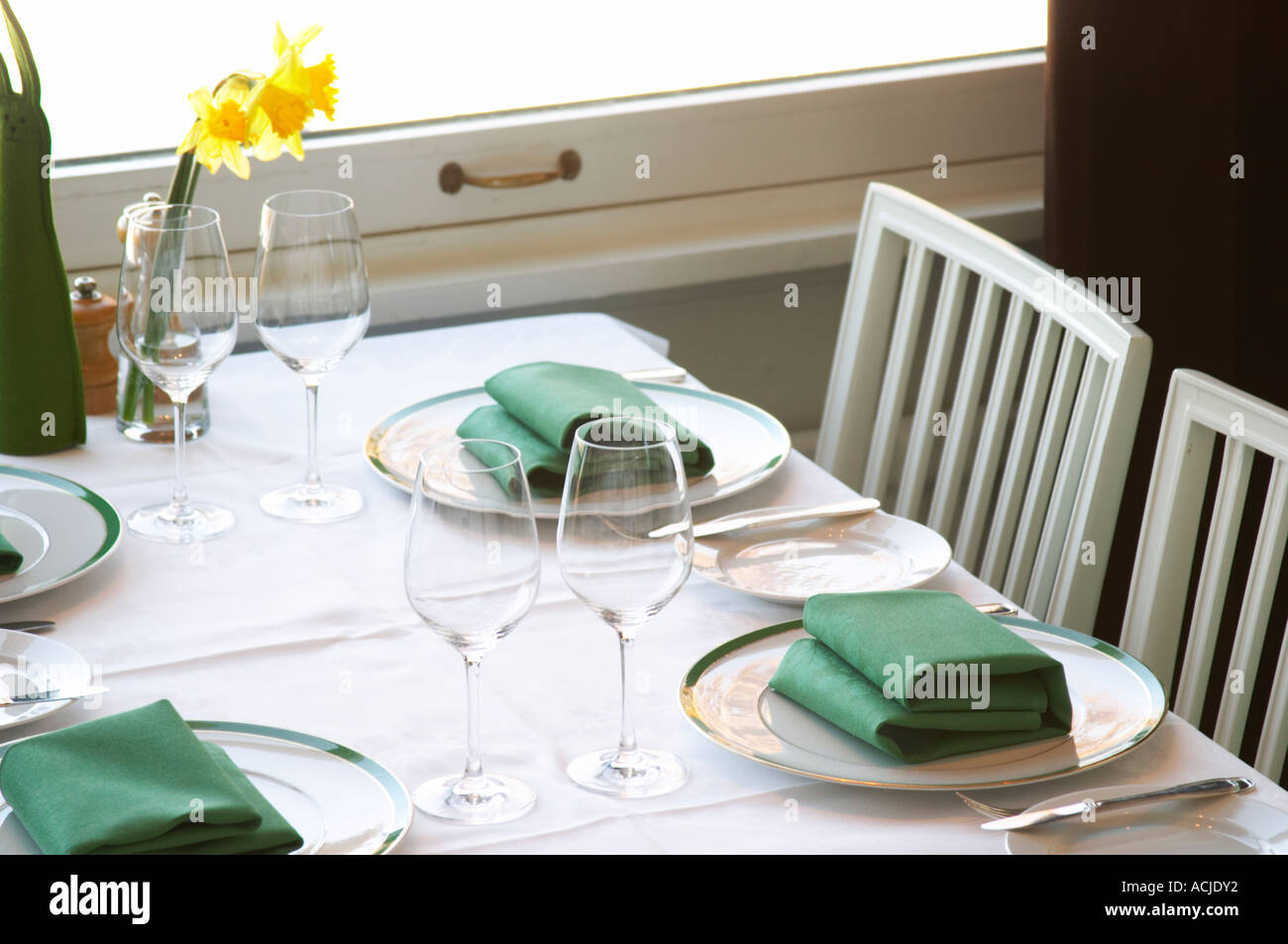 A restaurant table with a white linen table cloth set for four persons with plates silver cutlery and green napkins and a yellow Easter daffodil lily ... & A restaurant table with a white linen table cloth set for four Stock ...