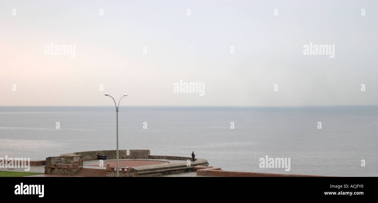 A view over the Rio de la Plata in Montevideo on a rainy day. A man alone standing on a viewing platform overlooking the water and the horizon line Rambla sur and Rambla Gran Bretagna along the River Rio de la Plata Montevideo, Uruguay, South America - Stock Image